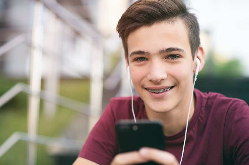 Close Up Portrait Of A Smiling Young Man With A Smartphone, In T