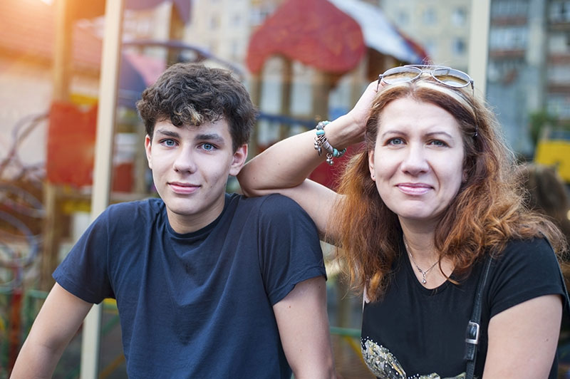Mom and teenage son talking about child psychiatry specialties